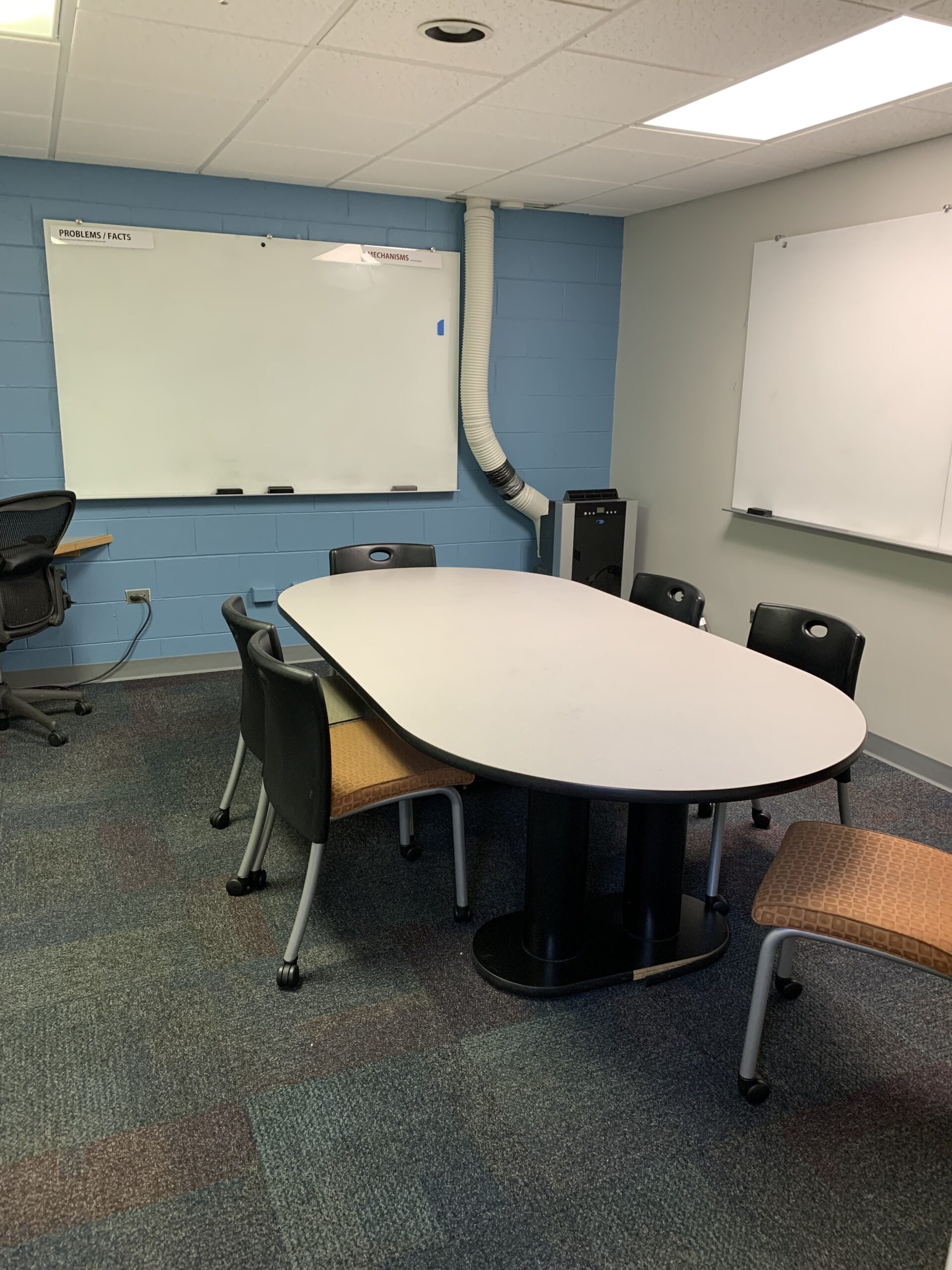 Table with seven chairs and two whiteboards